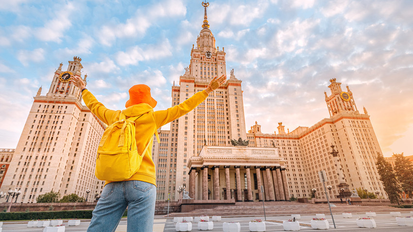 Mlad študent se veseli začetka šolskega leta pred glavno stavbo Moskovske državne univerze Lomonosova
