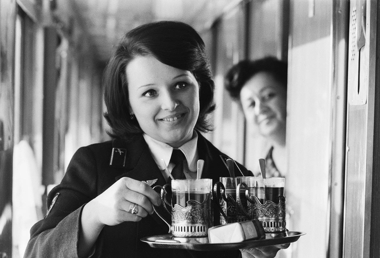 Kondektur kereta menyajikan teh dengan podstakannik.