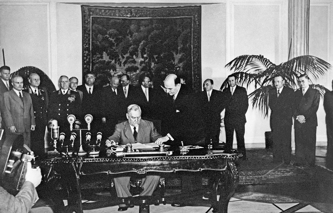 Председник Савета министара СССР-а Николај А. Булгањин (центар), потписује Уговор о пријатељству, сарадњи и узајамној помоћи између Албаније, Бугарске, Мађарске, ГДР-а, Пољске, Румуније, СССР-а и Чехословачке на Варшавском састанку европских држава за мир и безбедност у Европи 14. мај 1955.