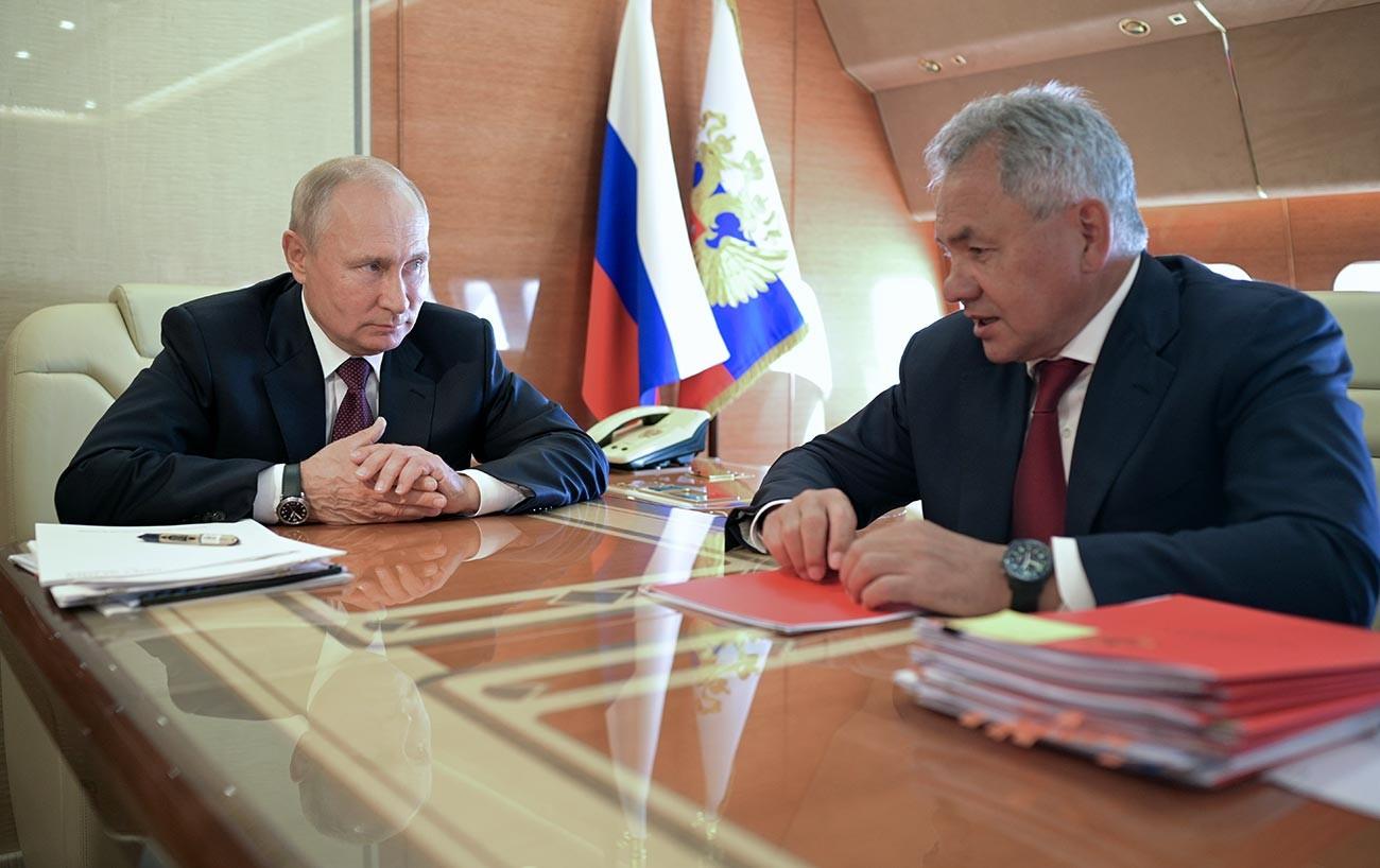 Presidente russo, Vladimir Putin, e o ministro da Defesa russo, Serguêi Choigu (à direita) reunidos a bordo, em julho de 2020