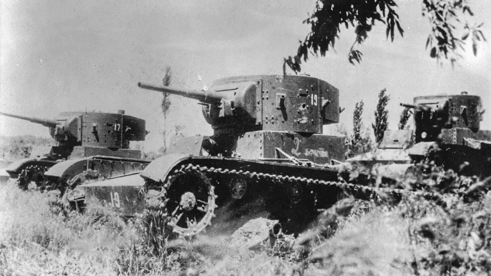 Três tanques leves T-26 fabricados na União Soviética percorrem campo durante batalha na  Guerra Civil Espanhola.