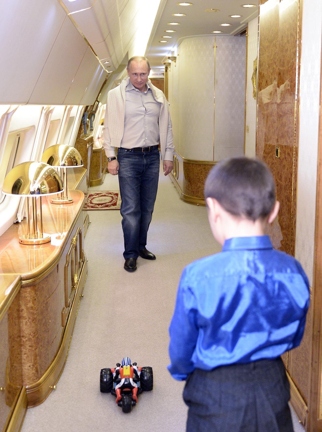 Президент России Владимир Путин и сын младшего сержанта Баира Банзаракцаева, погибшего при ликвидации последствий наводнения на Дальнем Востоке, Галсан играют на борту президентского самолета. 31 декабря 2013.