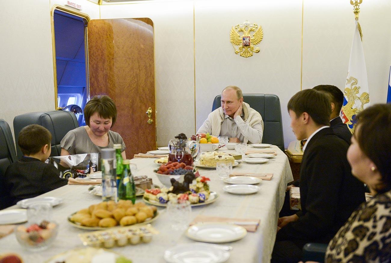 Vladimir Putin bersama keluarga Bair Banzaraktsayev, personel militer yang tewas saat bertugas dalam penyelamatan selama banjir di Timur Jauh Rusia.
