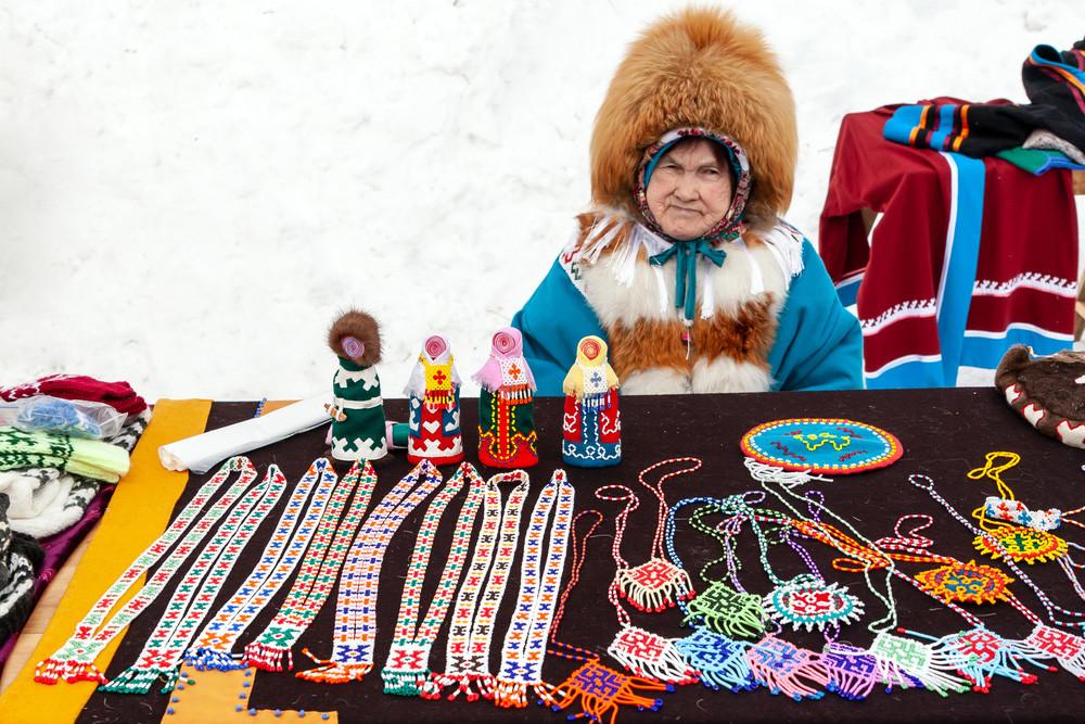 Женщина из народа ханты в национальной одежде продает сувениры на празднике оленеводов