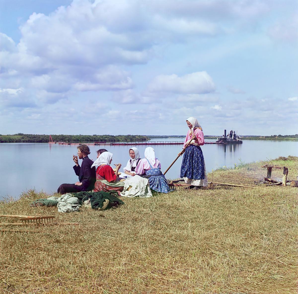 Cherepovets district. Peasants at tea break during hay gathering on island in Sheksna River. Background: dredging barge for navigation channel. Summer 1909
