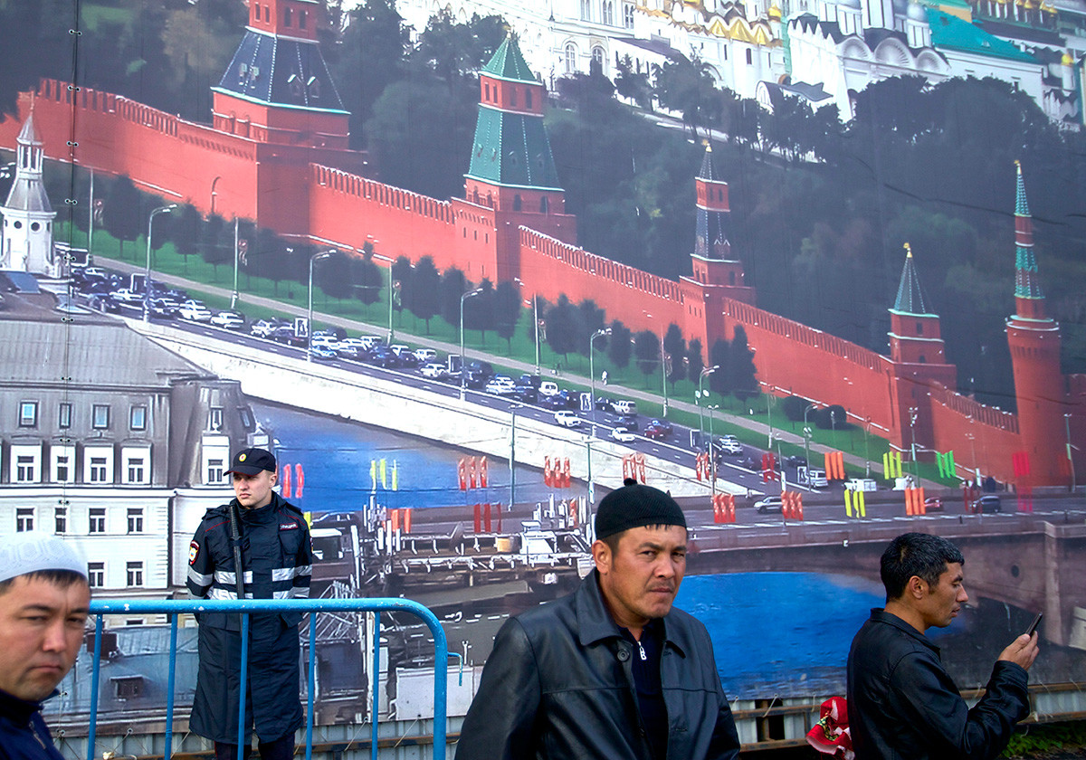 Muslim men, mostly migrant laborers from Central Asian countries, stand next to a fence decorated with picture of the Kremlin as they prepare for Eid al-Fitr prayers outside the Cathedral Mosque in Moscow, Russia, Tuesday, July 5, 2016