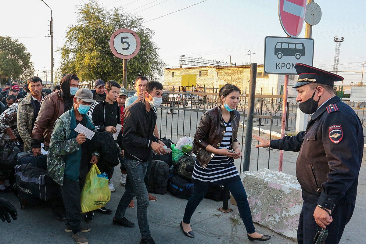 Police Officer Gestures To Uzbekistan S Citizens Who Have Arrived At A Railway Station Forecourt Before Being Repatriated. From March 16, Russia Temporarily Ceased Railway Communication With Uzbekistan To Prevent The Spread Of The COVID-19 Pandemic