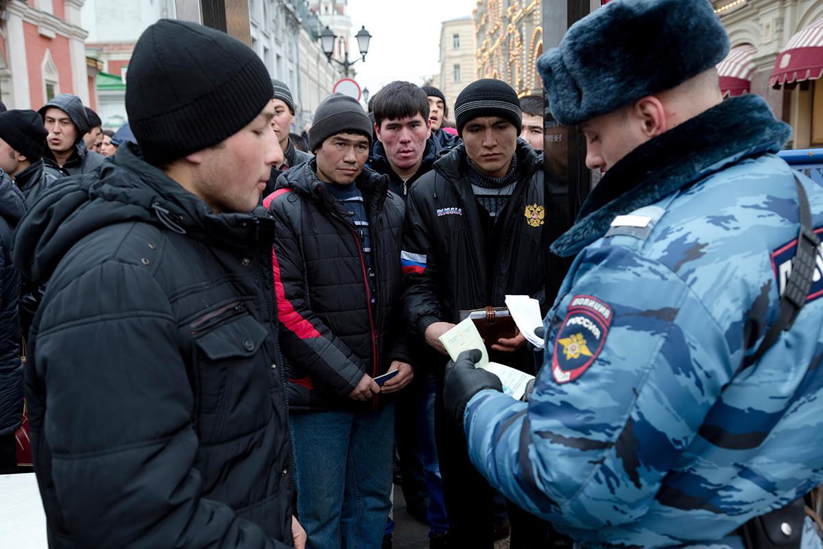 Policial verifica documentos de trabalhadores migrantes da Ásia Central na entrada da Praça Vermelha em Moscou