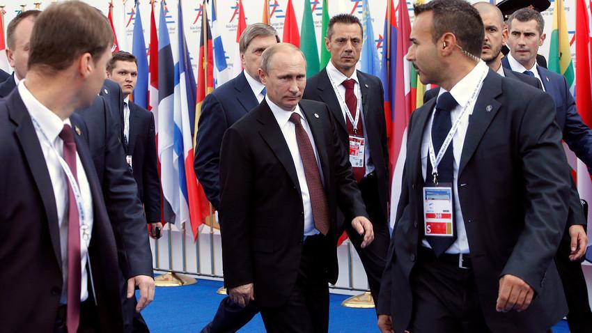El presidente de Rusia, Vladímir Putin rodeado por guardaespaldas a su salida de la cumbre Europa-Asia (ASEM) en Milán el 17 de octubre de 2014.