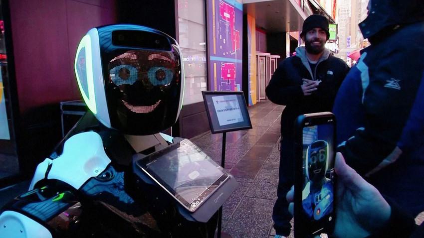 """Минувачи по """"Таймс Скуеър"""" разговарят с робота """"Промобот, който информира обществеността за симптомите на коронавирус и предотвратяването на разпространението му. Снимка от видео. Ню Йорк."""