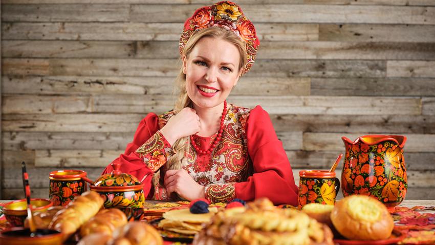 Жена у традиционалној руској ношњи са кокошником на глави за трпезом на којој се налази празнични хлеб.