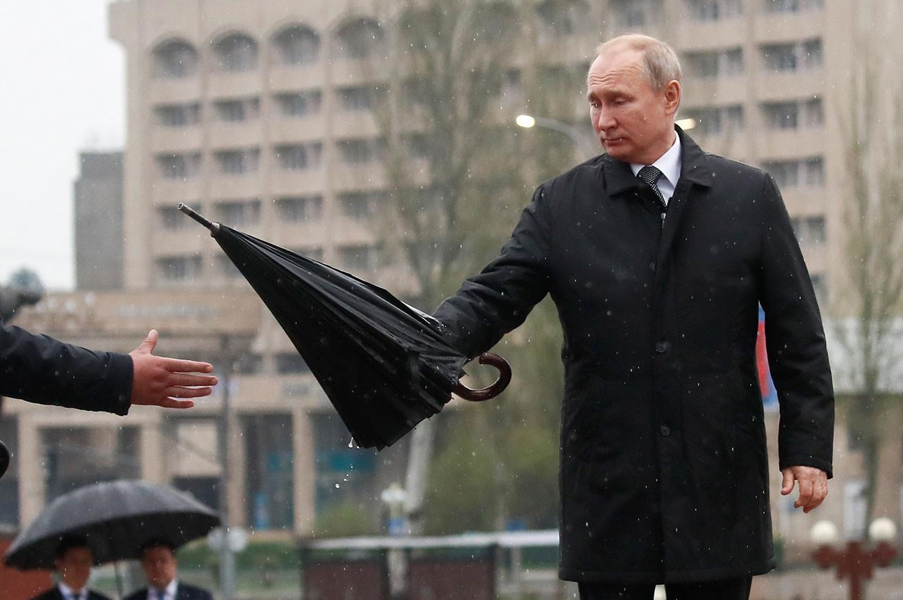 Putin predaja dežnik asistentu pred polaganjem cvetja pred obeležjem Večni ogenj v Biškeku v Kirgiziji, 28. marca 2019.