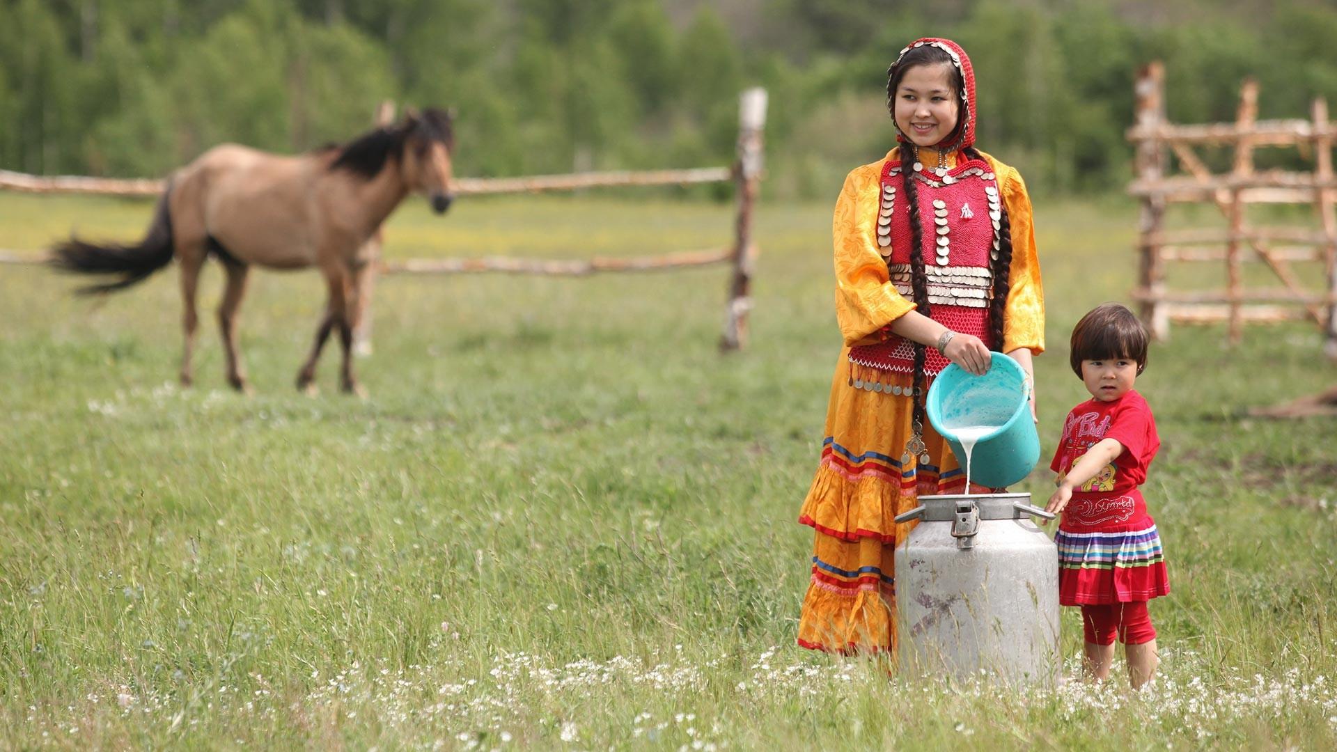 Memindahkan susu kuda ke dalam wadah khusu di sebuah peternakan pribadi untuk produksi kumis, minum khas setempat, di Republik Bashkiria.