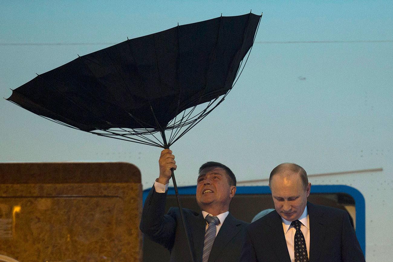 Служител по сигурността се бори с чадър, докато президентът на Русия Путин излиза от самолет при пристигане на летището преди четвъртата среща на върха на Конференцията за мерки за изграждане на взаимодействие и доверие в Азия (CICA), проведена в Шанхай. 19.05.2014 г.