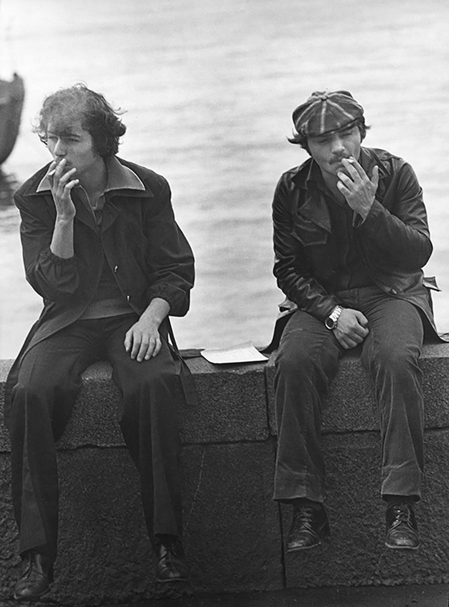 Zwei junge Männer machen eine Raucherpause, 1976.