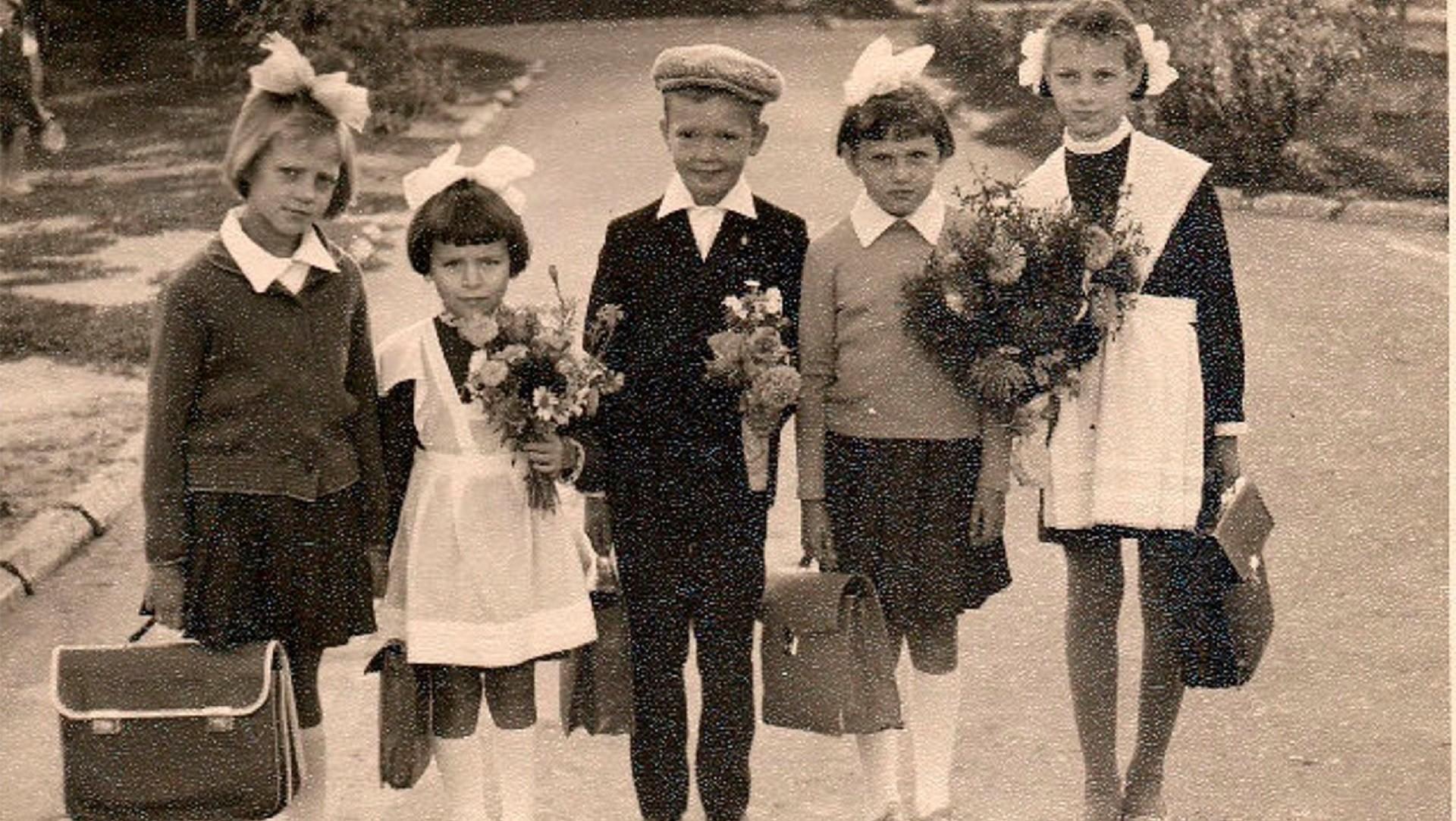 Crianças vestindo o clássico uniforme soviético.