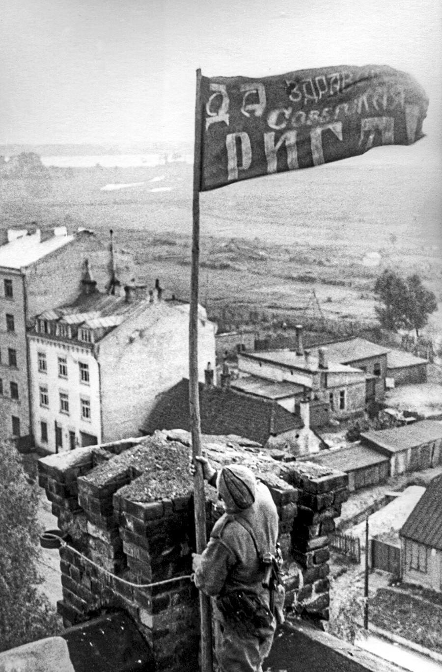 Рига, Летонска ССР, СССР. Војник истиче црвену заставу над градом након његовог ослобађања од немачко-фашистичких освајача током Другог светског рата.