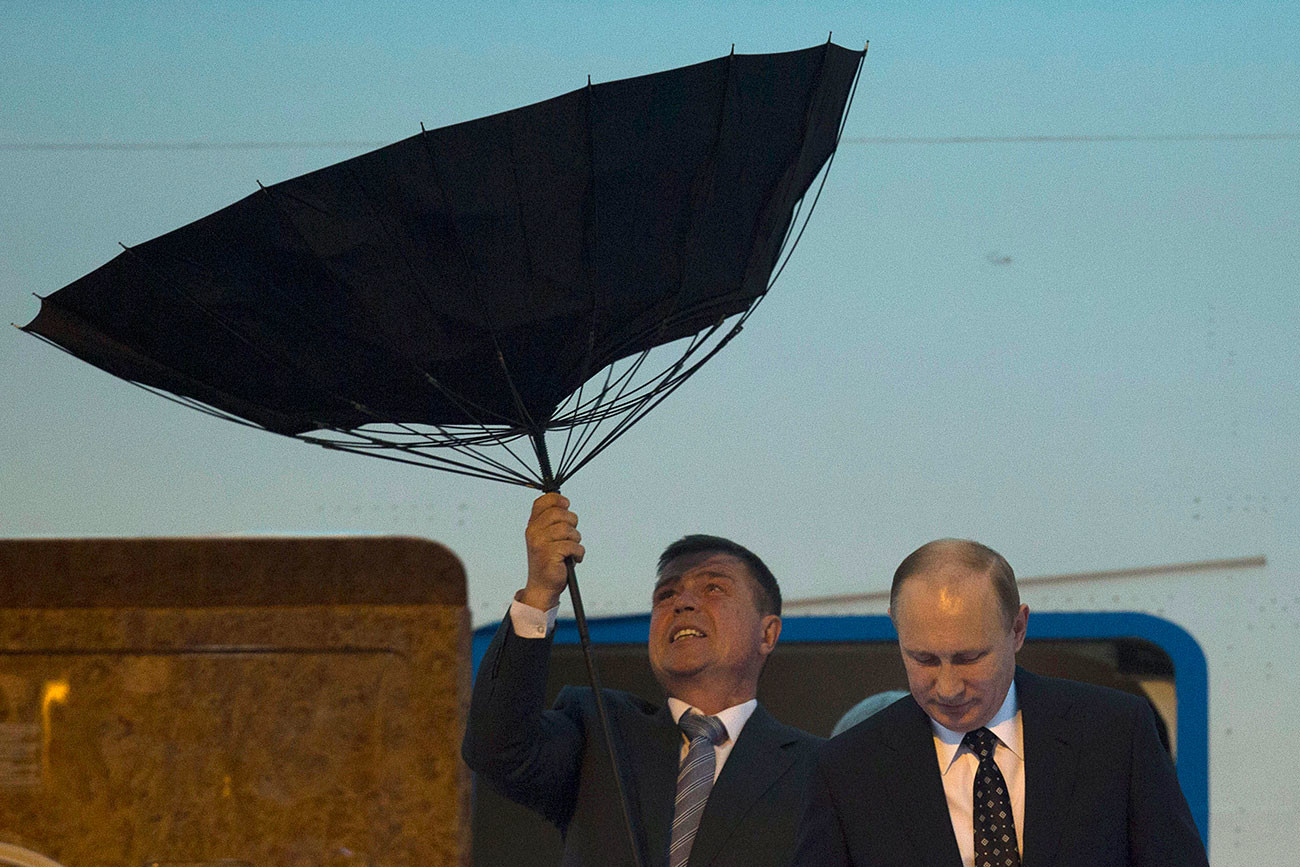 A security personnel struggles with an umbrella as Russia's President Putin walks out of a plane upon arriving at the airport ahead of the fourth summit of the CICA held in Shanghai. 19/05/2014