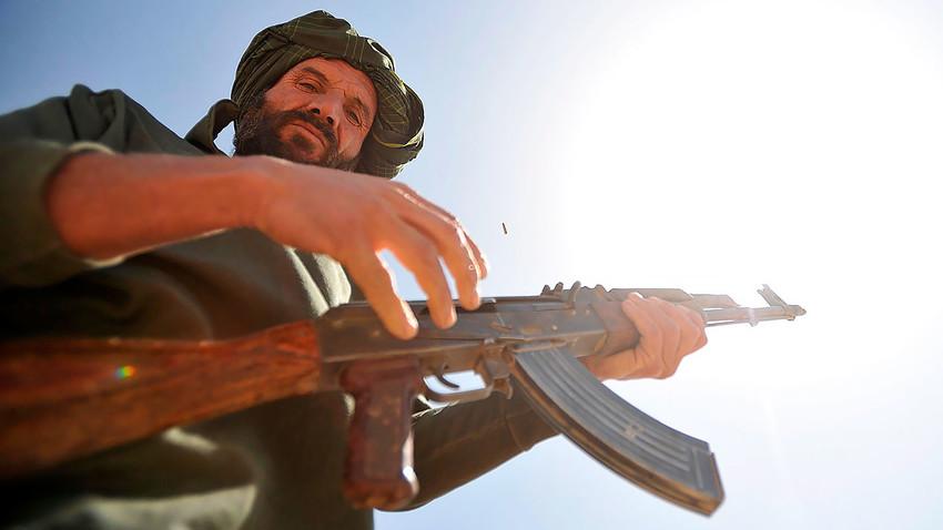 Seorang personel polisi Afganistan bersiap untuk menembakkan senapan AK-47 ke sasaran selama sesi pelatihan senjata di Distrik Nawbahar, Provinsi Zabul, Afganistan.