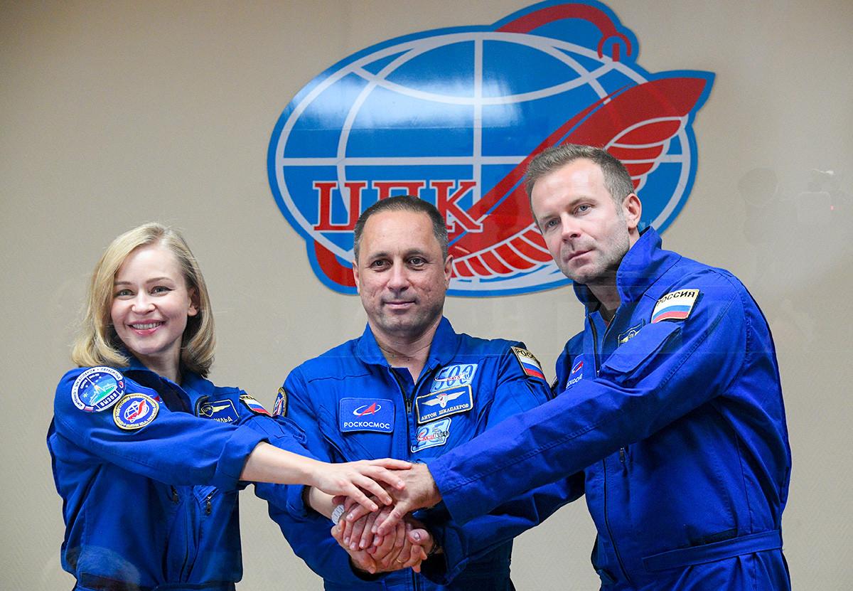 Членовете на основния екипаж на 66 -тата експедиция до Международната космическа станция, актрисата Юлия Пересилд, космонавтът Антон Шкаплеров и режисьорът Клим Шипенко (отляво надясно) на пресконференция на космодрума