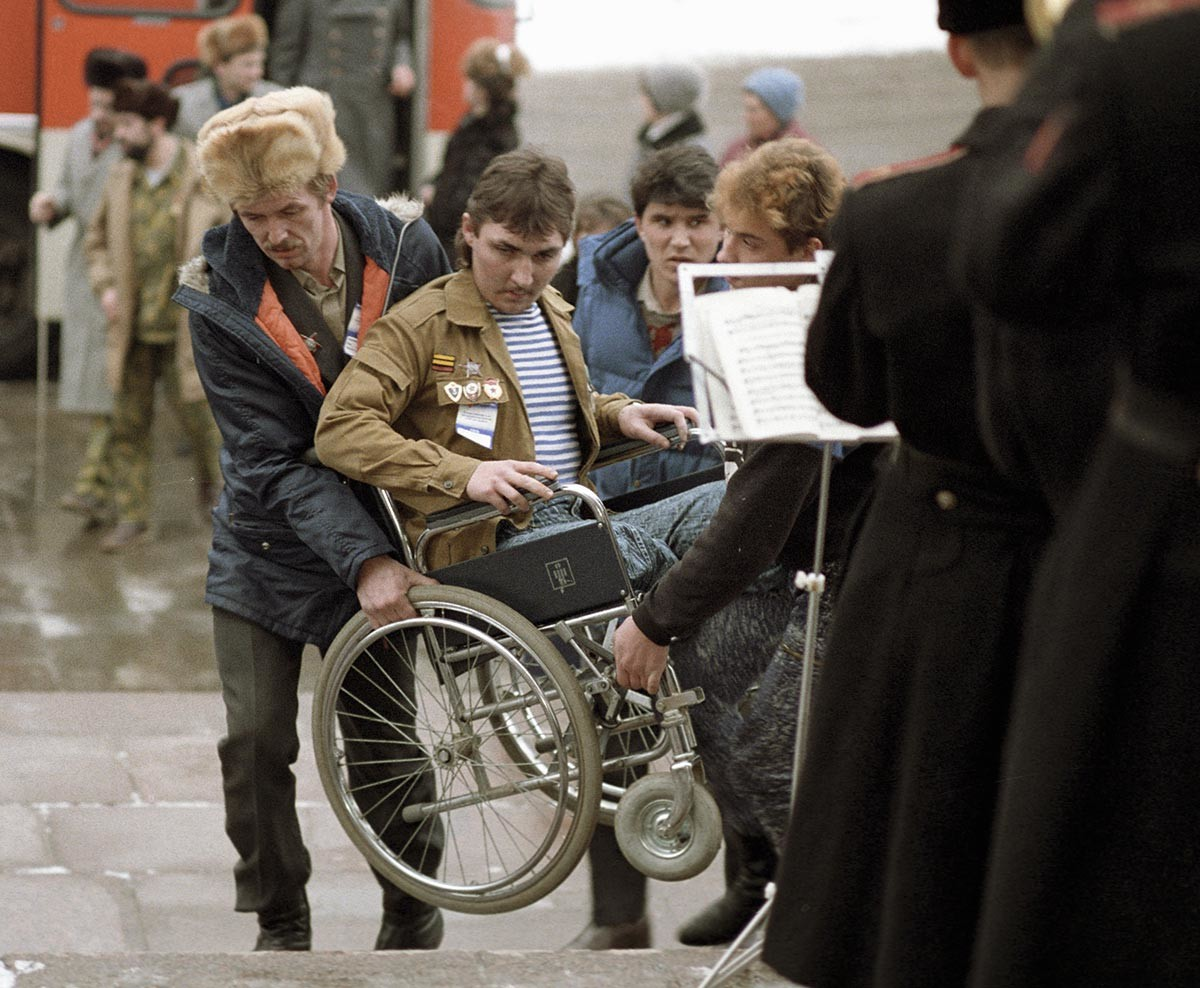 Several people helping a disabled vet of the war in Afghanistan to get up the stairs in his wheelchair, 1990.