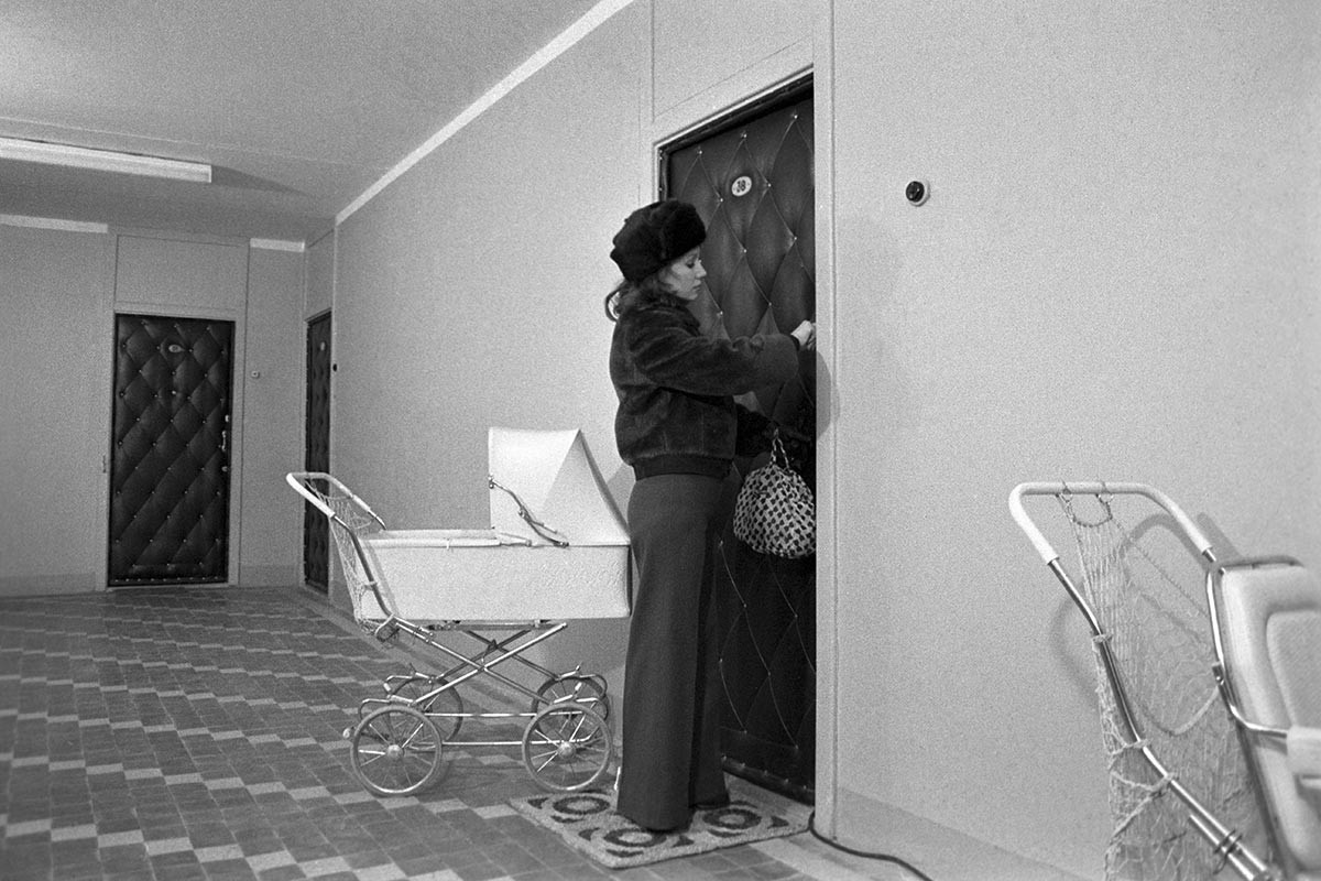 A woman opening a door covered in fabrikoid (dermatin), cheap artificial leather.