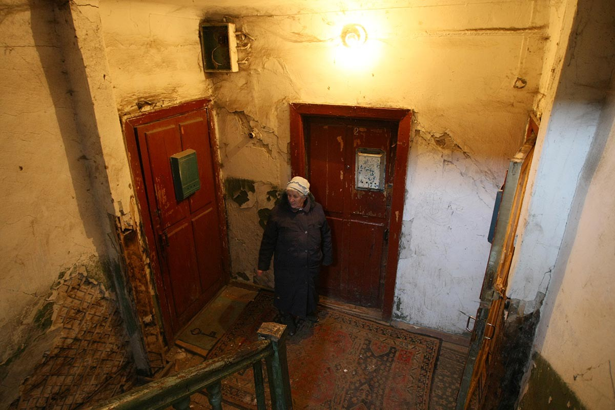 A woman standing in the staircase of her apartment house in Novosibirsk, Russia. Notice the old wooden doors.