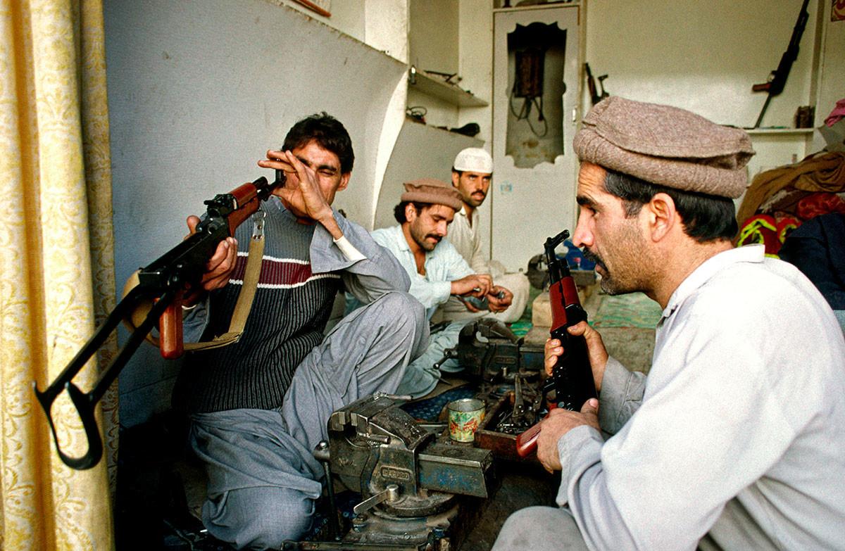Pembuat senjata Pakistan dari Darra Adam Khel memeriksa senjata AK-47 Kalashnikov.
