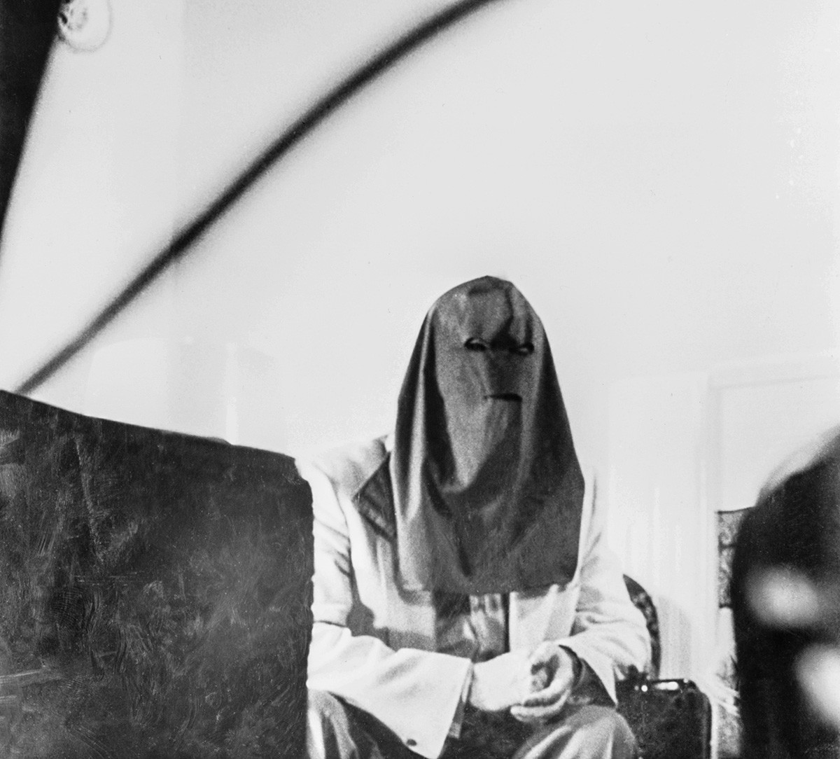 Igor Gouzenko, former decoding clerk in the Russian Embassy in Toronto who exposed a Red spy ring operation in Canada, is shown in the first photo ever permitted of him since he became a marked man...He is wearing a specifically designed hood to foil future identification.