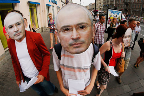 Russian opposition protesters wearing masks depicting jailed tycoon Mikhail Khodorkovsky march downtown St.Petersburg marking his 50th birthday, Russia, Wednesday, June 26, 2013. credit AP