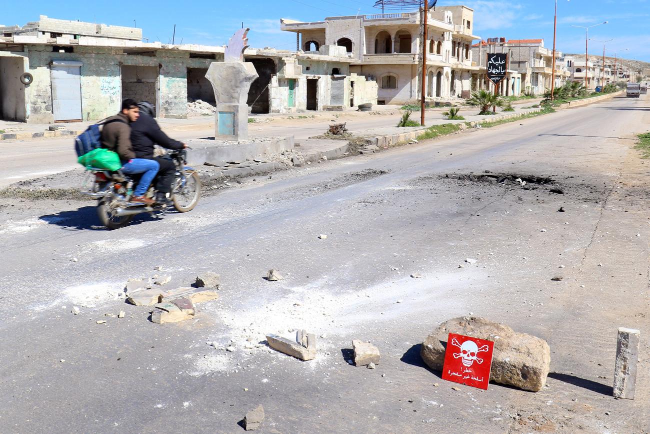 "Dua orang pria di atas sepeda motor melewati tanda bahaya di lokasi serangan udara di kota Khan Sheikhoun di Provinsi Idlib yang dikuasai pemberontak, Suriah, 5 April 2017. Tanda bahaya itu berbunyi, ""Bahaya, amunisi yang belum meledak."" Sumber: Reuters"