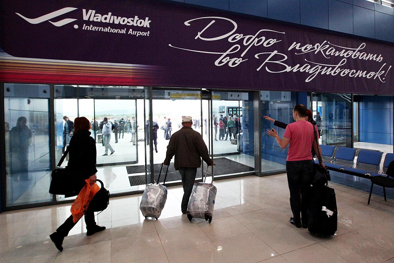 Para penumpang meninggalkan terminal internasional yang baru setelah pesawat mendarat di Vladivostok. Sumber: Vitaliy Ankov/RIA Novosti