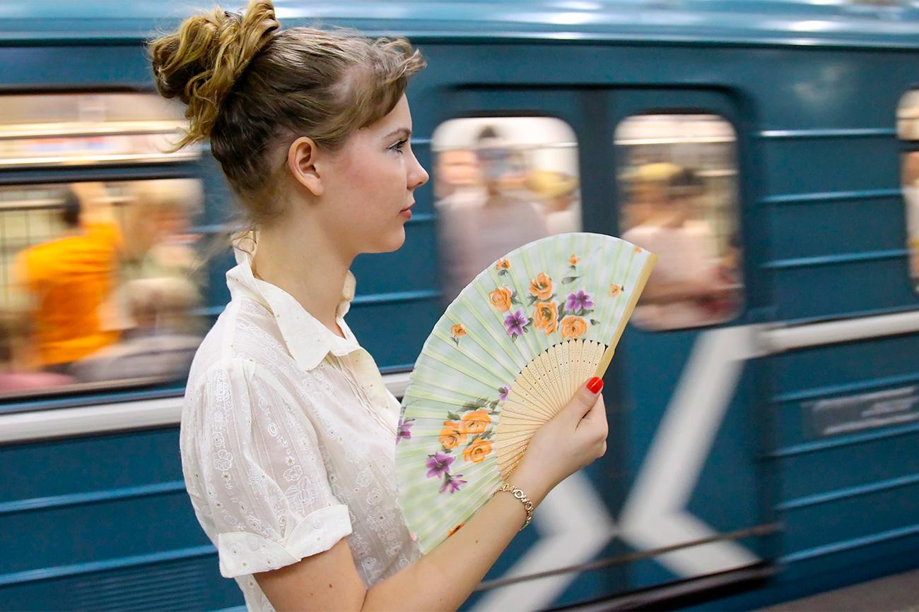 Seorang perempuan muda mengipasi dirinya di sebuah stasiun metro Moskow. Sumber: Vladimir Fedorenko/RIA Novosti