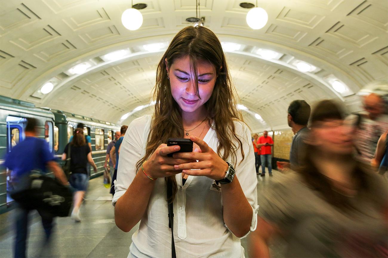 Seorang perempuan muda sedang bermain Pokemon Go di Stasiun Biblioteka Imeni Lenina. Sumber: Mikhail Tereshchenko/TASS