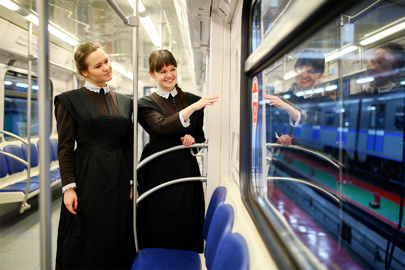 Dua orang perempuan mengenakan seragam siswa zaman dulu di Plekhanovets, kereta bawah tanah terbaru Moskow dalam rangka ulang tahun ke-110 Universitas Ekonomi Rusia Plekhanov. Sumber: Kantor Pers Metro Moskow/TASS