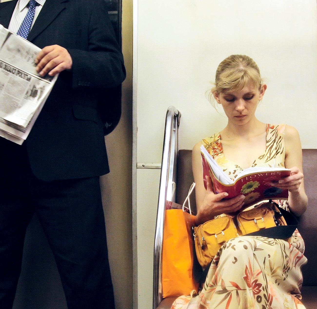 Seorang gadis sedang membaca buku pelajaran di dalam metro Moskow. Sumber: Marina Lystseva/TASS