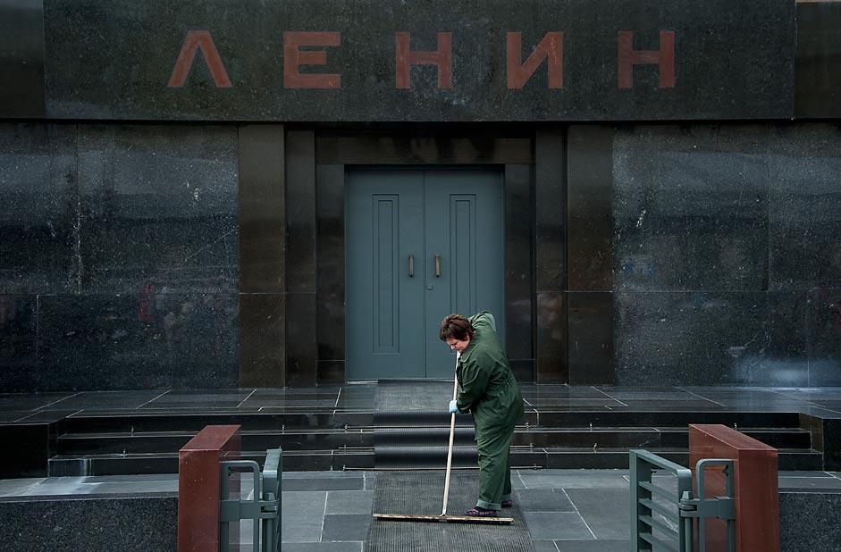 Un&#39addetta alle pulizie del Comune di Mosca spazza l&#39ingresso del Mausoleo di Lenin in Piazza Rossa
