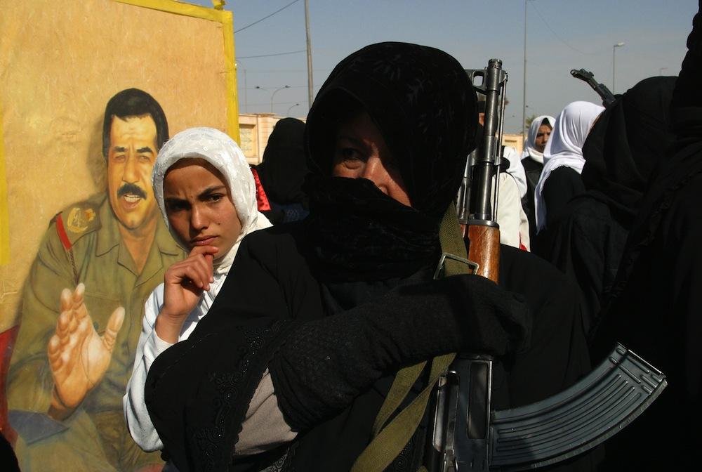 Perempuan Irak menggenggam senapan AK-47 di depan foto mantan Presiden Irak Saddam Hussein.