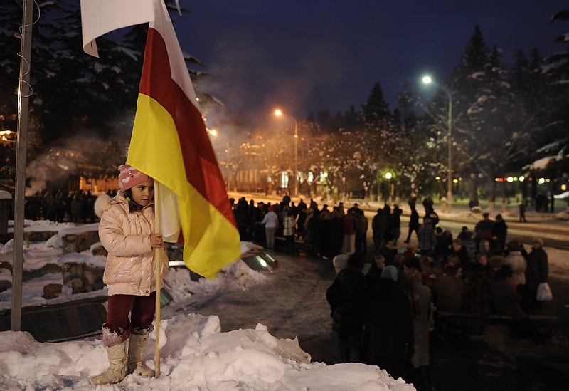 A girl holding the South Ossetia's flag in the central square of Tskhinvali