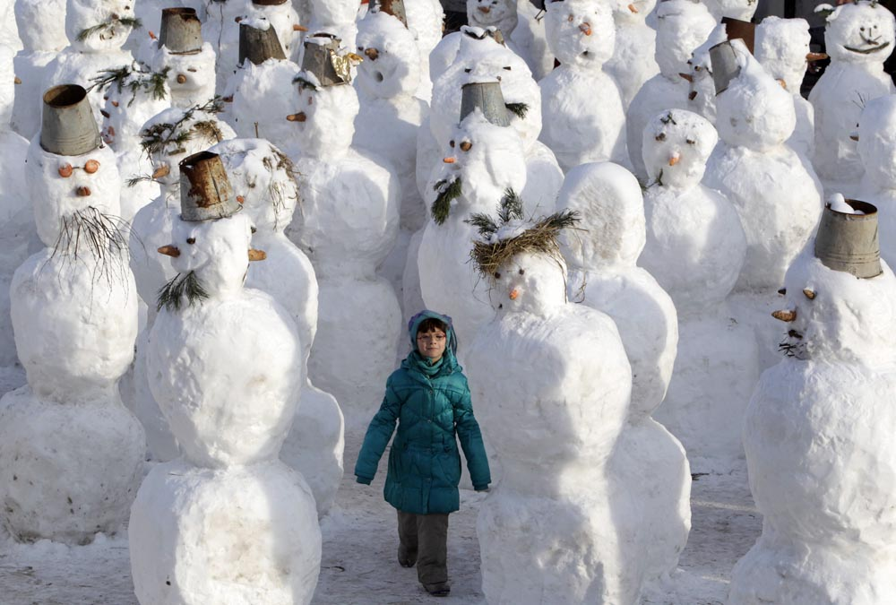 A girl walks among snowmen built as part of a display on a street in Moscow.