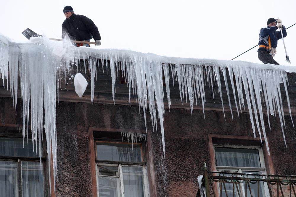 Municipal workers breaking dangerous icicles from the roof of a building in downtown in St Petersburg.