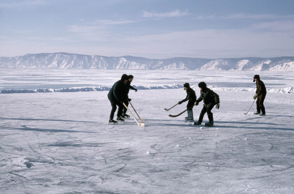 Boys play hockey on a frozen part of Lake Baikal which they have cleared of snow.