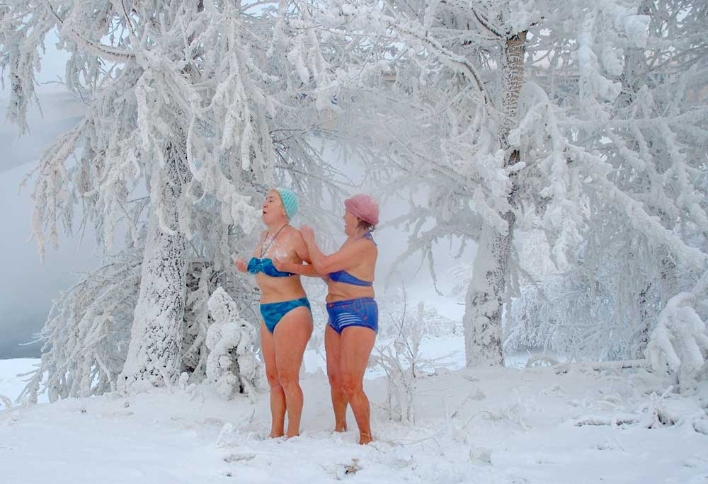 A woman rubs the back of another woman with snow while standing between trees covered in hoarfrost after taking a bath in the Siberian river of Yenisey in Krasnoyarsk. The members of the local ice-bathing club enjoyed a swim in the icy water of the Yenisey River at temperatures of around -28 C (-14.8 F)