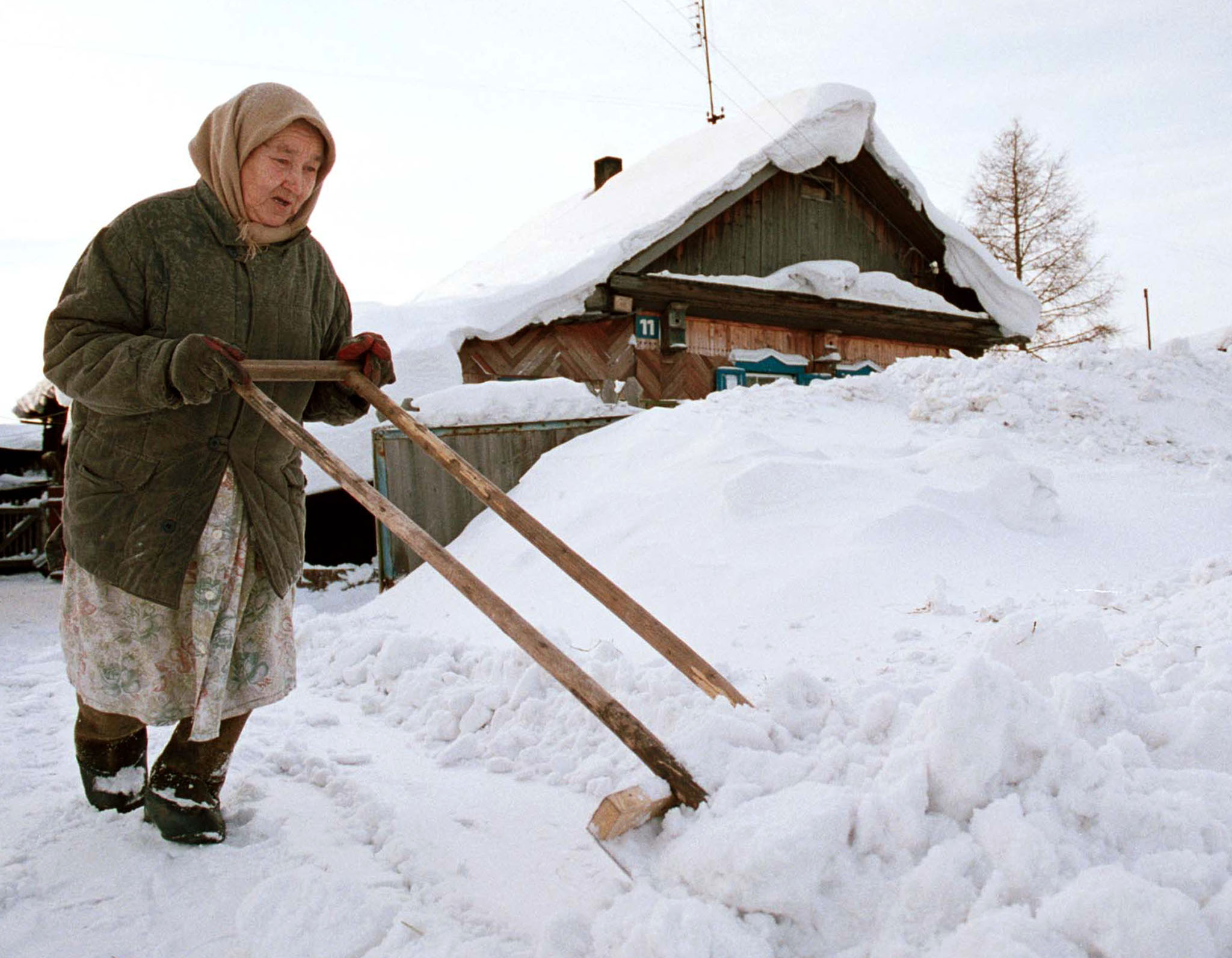 An old woman cleans snow in a settlement Beregovoi outside the Siberian city of Kemerovo.