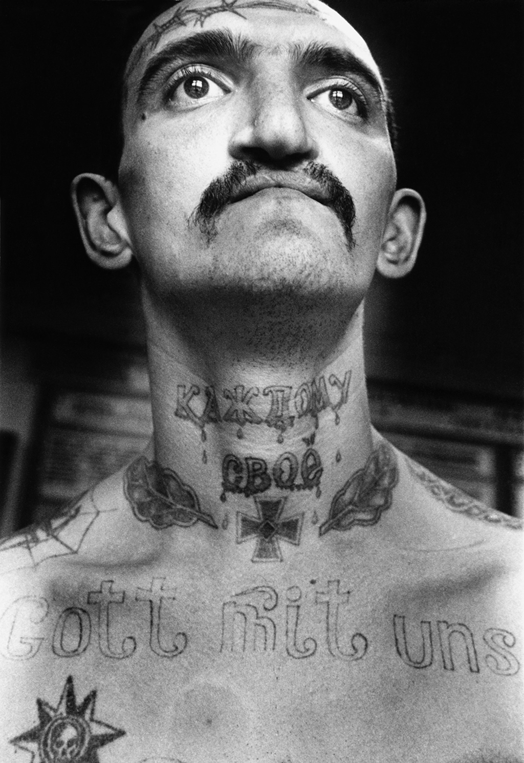 This inmate was convicted for drug related crimes. 'Gott mit uns': 'God with us' was a rallying cry of both the Russian empire and the Third Reich. The Nazi Iron Cross expresses 'I don't care about anybody'. This symbol of aggression and insubordination is often tattooed on the chest tattooed as if hung on a chain. The barbed wore on the forehead denotes that the bearer 'will never be corrected'.