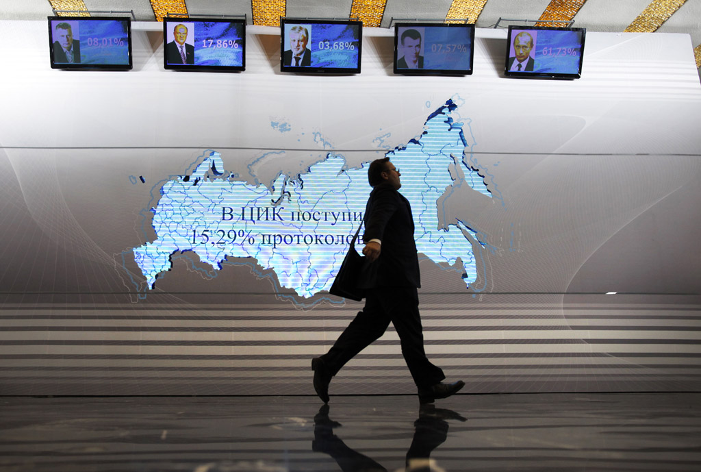 A man walks past a map of Russia and portraits of presidential candidates, from left: Vladimir Zhirinovsky, Gennady Zyuganov, Sergei Mironov, Mikhail Prokhorov and Vladimir Putin at the Putin's headquarters in Moscow, Russia, March 4, 2012. Prime Minister Vladimir Putin won Russia's presidential election on Sunday, according to exit polls cited by state television, but the vote was tainted by widespread violations claimed by the opposition and independent observers.