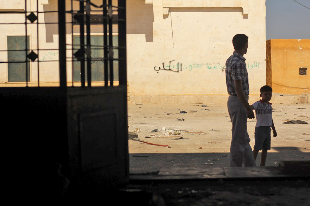 Seorang bapak menggandeng tangan putranya di tengah kota Azaz, Suriah, yang telah hancur.