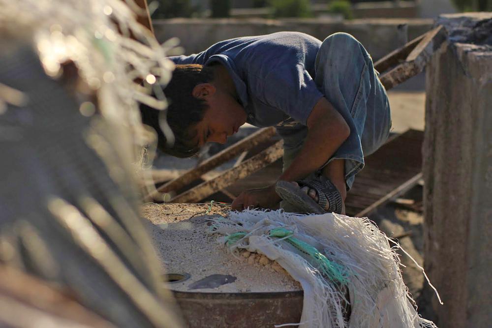 Seorang anak di atas reruntuhan atap sekolah di Azaz, barat laut Suriah.