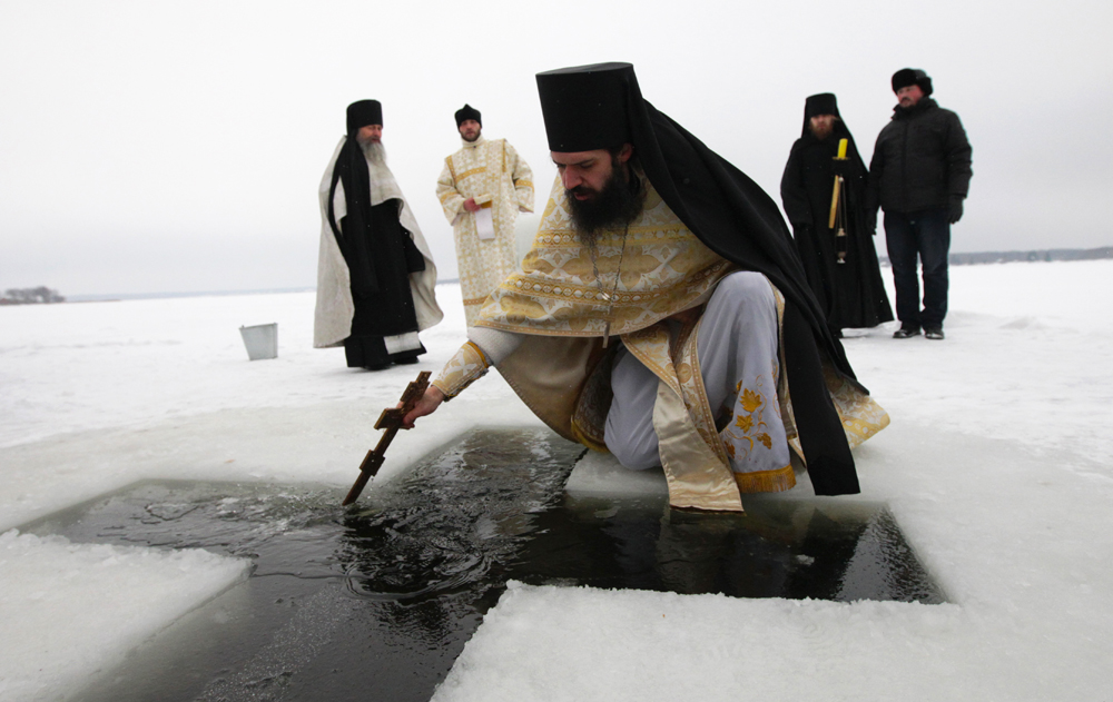 "Priests and regular believers from many different churches go down to a lake or a river, where a hole has been cut into the ice in the shape of a cross. This opening in the ice is called a ""jordan,"" in honor of the holy River Jordan, in which Jesus was baptized. (Vologda region, Russia)"