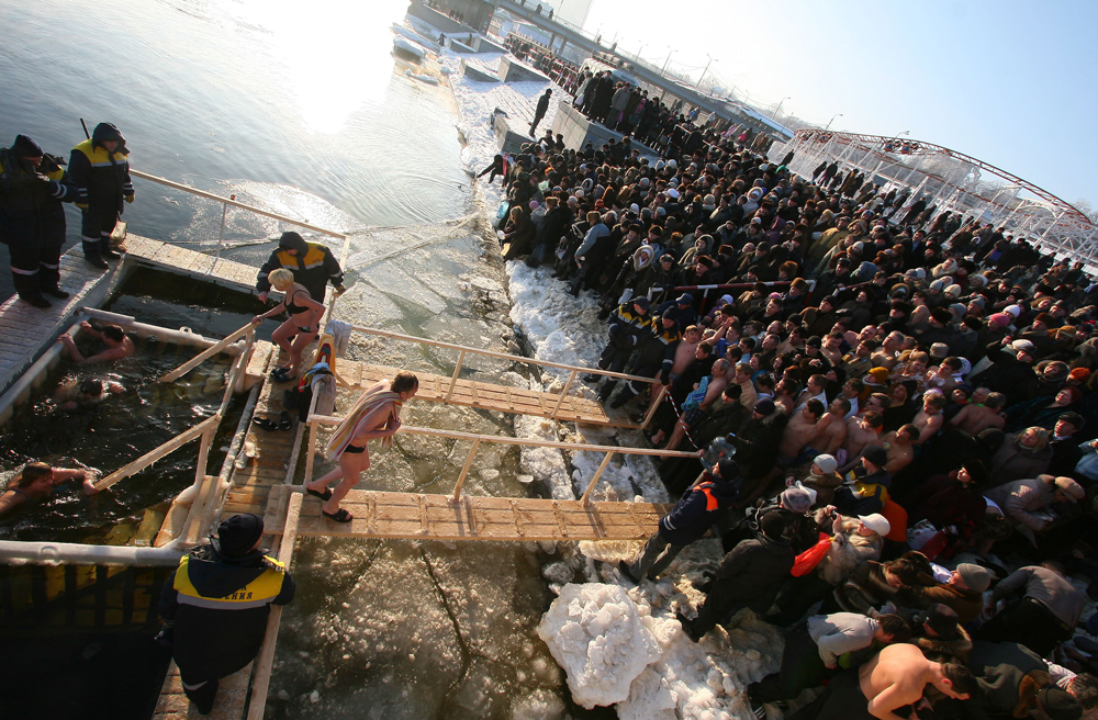 People climb down into the jordan on a small wooden ladder until they are half submerged, then they make the sign of the cross before fully submerging themselves in the water three times. (Volgograd region, Russia)